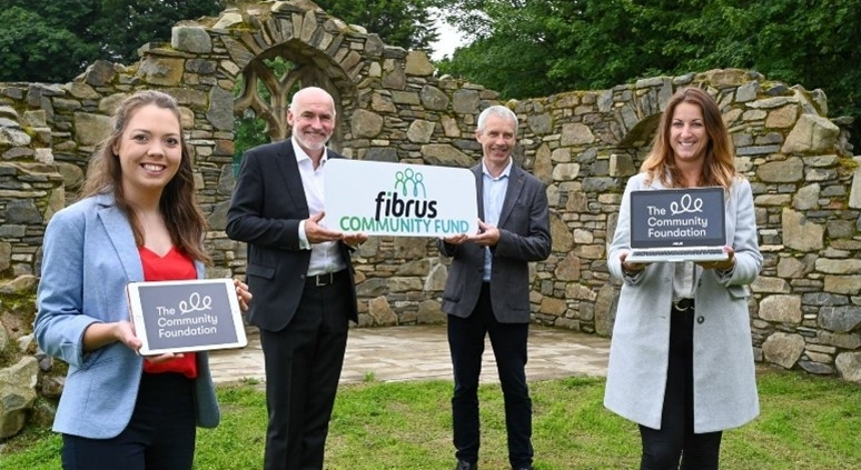 Two men and two women holding signs saying 'Fibrus Community Fund' and 'The Community Foundation'